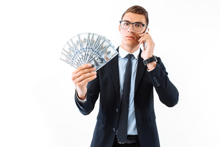 Successful businessman in glasses and suit, talking on the phone, holding dollar bills looking at them, on a white background