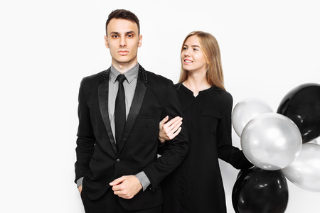 beautiful stylish couple, a young girl in a black dress and a man in a black suit, in the hands, balloons and bags, for shopping on a white background. Concept of shopping, discounts, black friday