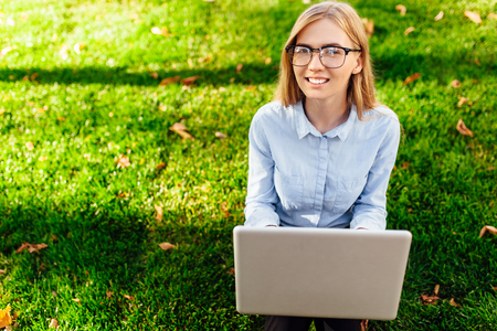 Image of a young amazing lady, sitting in a park, using a laptop computer, sits on a green lawn.