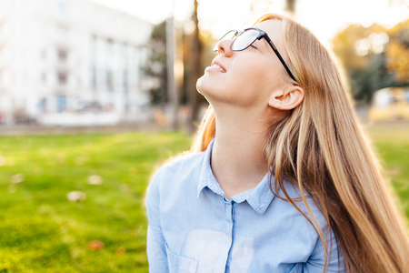 happy girl with glasses breathe fresh air, enjoy the warmth, outside Imagens