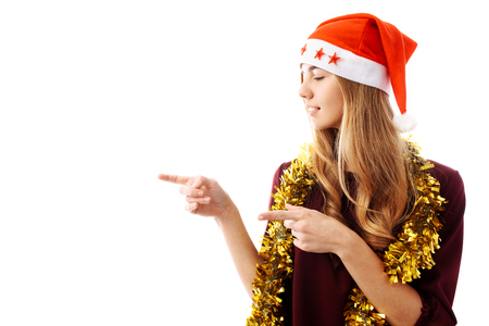 Portrait of a beautiful girl, wearing a Santa Claus hat, points her finger into a blank space, isolated on a white background. Christmas Stock Photo