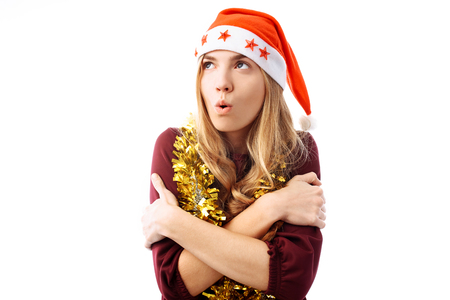A young girl wearing a Santa hat is cold and she is warming up, for white background. Christmas, winter