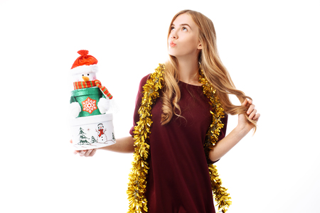 Pensive young woman, wearing a Santa Claus hat, dreams, looking to the side, in her hands, a gift box on a white background. Christmas