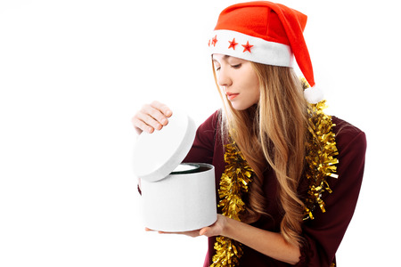 An interested girl in a Santa hat, looks in a gift box, on a white background. a Christmas gift