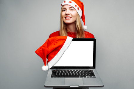 Portrait of happy woman in red sweater and santa claus hat, showing blank laptop screen, looking at camera, on gray background. Christmas Foto de archivo - 112889684