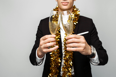 attractive man in a business suit, and with a tinsel around his neck, a man holding a glass of champagne, on a gray background. The concept of the new year.