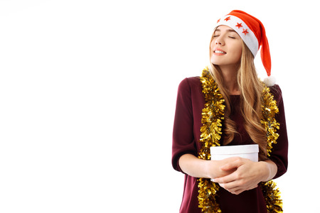 Pensive young woman in a Santa Claus hat, received a long-awaited Christmas gift on a white background. Christmas