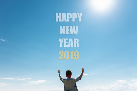 Man in the background, blue sky. Text Happy New Year, on clouds, christmas concept.