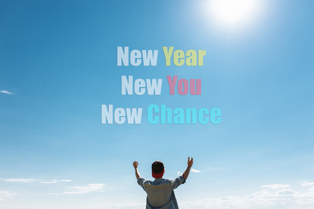 The guy pulls his hands to the sky on which the text. new year, new me, new chance. concept, christmas