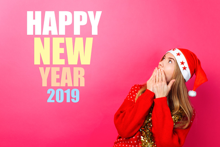 girl in a santa hat with a tinsel around her neck, pointing fingers up and showing a blank space with text. Happy New Year. on a red background. Christmas concept.