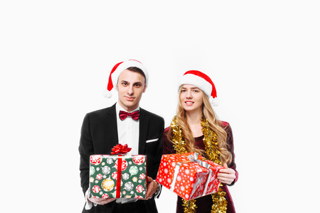 Happy couple of lovers, in Santa Claus hats with Christmas gifts in their hands. On a white background. Stock Photo