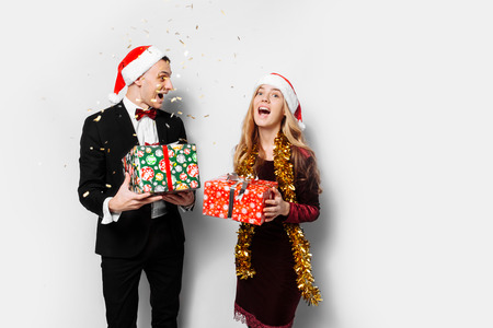 A stunned pair of lovers in Santa Claus hats celebrating the new year and giving each other Christmas presents. on a white background Stok Fotoğraf