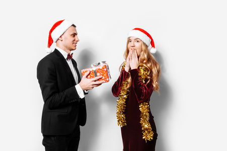 A happy couple of lovers, in Santa Claus hats, the guy gives a girl a Christmas gift. On a white background. 免版税图像 - 113092868