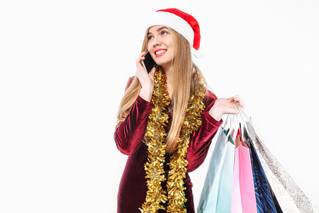 Beautiful woman in santa hat, with christmas bags in hand, talking on smartphone. On a white background. Stockfoto
