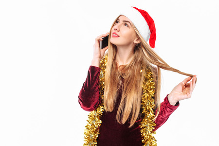 Happy girl in santa hat talking on mobile phone. On a white background Stockfoto