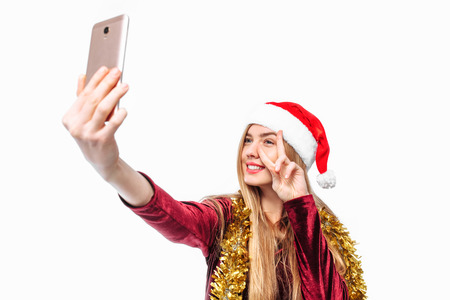 Happy woman in santa hat and dress, shoots herself, on smartphone. on a white background
