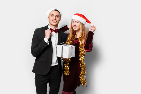 A happy couple of lovers, in Santa Claus hats, celebrates the New Year, with Christmas gifts in their hands. On a white background. Stok Fotoğraf