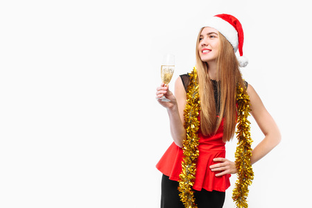 Happy young woman wearing a dress and Santa hat, celebrating the new year, in her hands, a glass of champagne, on a white background. Christmas concept.