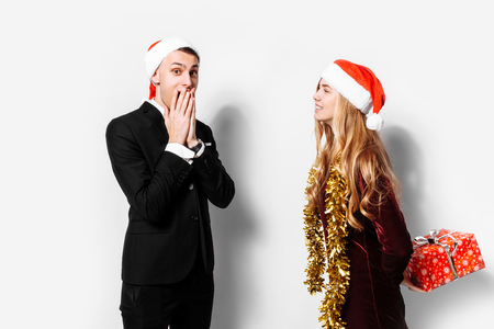 A happy couple of lovers, in Santa Claus hats, the girl gives the guy a Christmas present. On a white background. Stok Fotoğraf