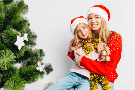 Mom and daughter are dressed in Santa Claus hats, in New Year's sweaters, daughter hugs mom, sits near the Christmas tree. On a white background. Reklamní fotografie