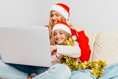 Beautiful young mother and her little daughter dressed in Santa Claus hats using a laptop and smiling while sitting on the sofa at home. Christmas concept