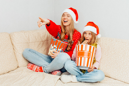 A young mother and her little daughter, dressed in Santa Claus hats, are watching movies and eating popcorn while sitting on the couch at home. Christmas concept