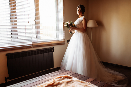 bride poses by the window in a hotel room Reklamní fotografie
