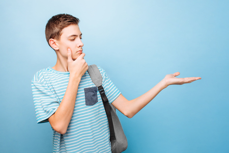 Pensive teenager looks into the camera, pointing a finger at an empty space, on a blue background