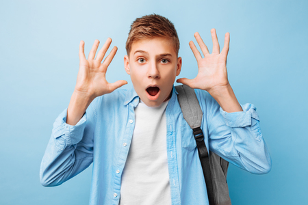 Depressed emotional teenage guy raises his hands and desperately exclaims, annoying facial expression, on a blue background