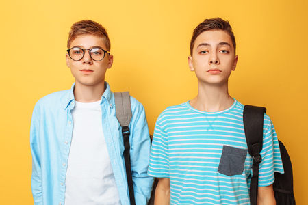 Portrait of two happy stylish guys, friends, isolated on yellow background