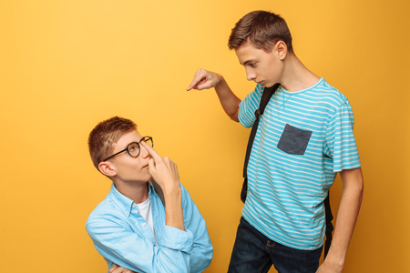Two teenage friends, one guy humiliates the other, popular humiliates the unpopular Фото со стока