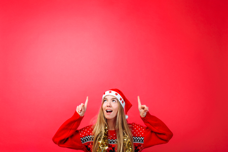 Beautiful surprised girl in Santas hat, with tinsel on her neck pointing fingers up and showing a blank copy space on a red background. The concept of Christmas advertising Stok Fotoğraf