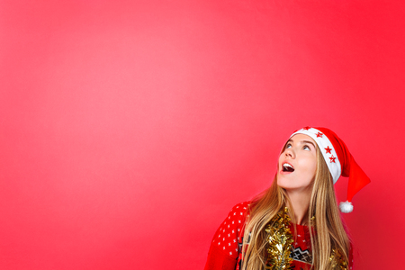 A beautiful surprised girl in Santas hat, with tinsel on her neck, looks at the empty copy space on a red background. The concept of Christmas advertising