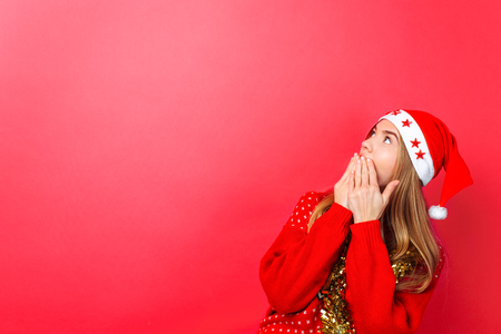 Beautiful surprised girl in Santa hat, with tinsel on her neck, delighted with something, looks at the empty copy space on a red background. The concept of Christmas advertising Stok Fotoğraf
