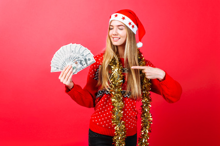 A successful girl in a red sweater and Santa hat holds the money on a red background and points her finger at . The concept of a Christmas business