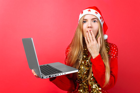 Shocked girl in red sweater and Santa hat, with laptop in hand, depicts surprise and looks at the camera closing her mouth on a red background Foto de archivo - 114117259