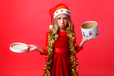 Frustrated teen girl in Santa hat and with tinsel on her neck, with disappointment holding empty box on red background