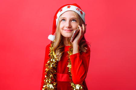 Happy girl in Santa's red hat and with tinsel on her neck, teen talking on the phone, congratulating on New year and Christmas