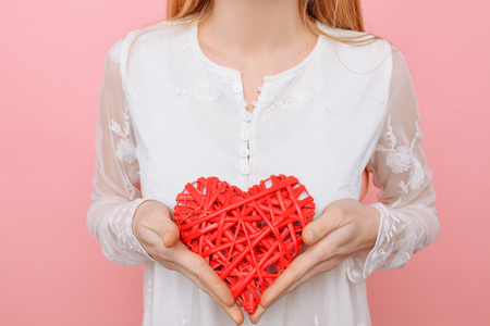 Beautiful girl in love holding a red heart, valentine, on a pink background Stock fotó