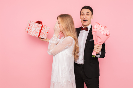 Handsome man in a suit making a surprise to a woman, closing her eyes with her hands on a pink background