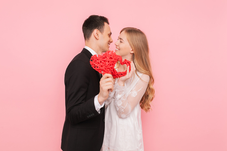 Couple in love, man and woman holding red hearts, on pink background, lovers day