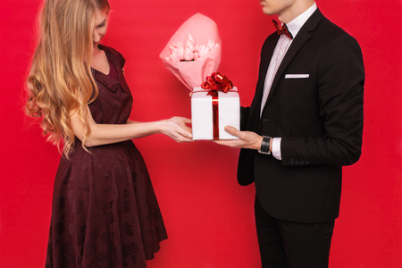 An elegant man in a suit gives a box with a gift and a bouquet of flowers to a beautiful woman on a red background. Womens day concept