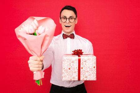 man, wearing glasses, with a gift and a bouquet of flowers, on a red background, the concept of women's day