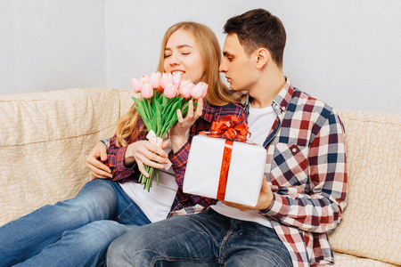 Young couple in love, man congratulates woman, giving her a bouquet of tulips and a gift, sitting on a sofa at home, concept of women's day