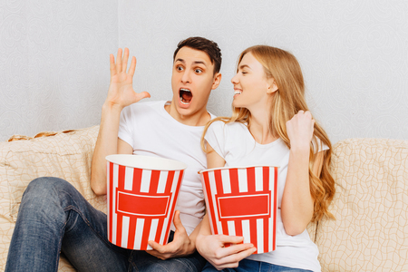 Beautiful young couple, man and woman, smiling, watching movies and eating popcorn, sitting at home on the couch 스톡 콘텐츠