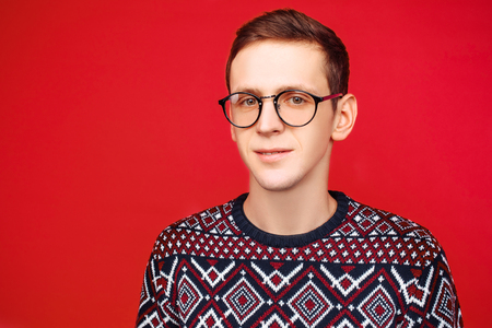 A man with glasses and a sweater, on a red background