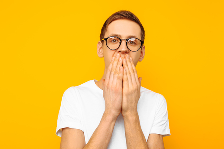 Portrait of a frightened man with glasses, a guy dressed in a white T-shirt, covering his mouth with his hands for fear, on a yellow background