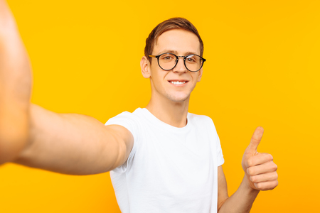 Portrait of a man wearing glasses and a white t-shirt showing thumbs up taking a selfie on yellow background