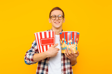 Portrait of a happy man in transparent glasses with a bucket of popcorn, keen on watching a film, in a plaid shirt, isolated on a yellow background