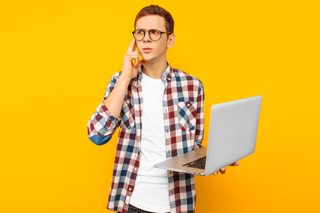 thoughtful man with laptop, on yellow background